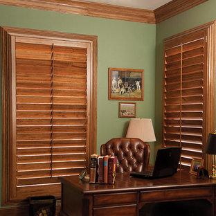 Inspiration för mellanstora klassiska hemmabibliotek, med gröna väggar, mörkt trägolv, ett fristående skrivbord och brunt golv