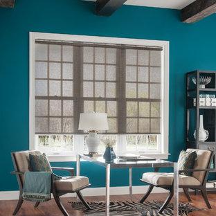 Cette image montre un grand bureau design avec un mur bleu, un sol en bois brun et un bureau indépendant.