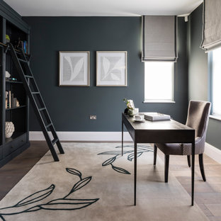 Inspiration for a large contemporary home office in London with grey walls, medium hardwood flooring, a freestanding desk and brown floors.