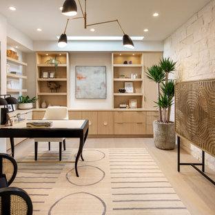 Modernes Arbeitszimmer mit beiger Wandfarbe, braunem Holzboden, freistehendem Schreibtisch und beigem Boden in Orange County