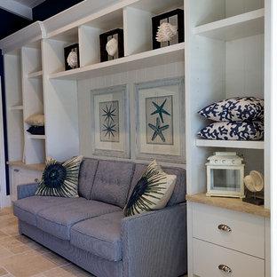 Идея дизайна: рабочее место среднего размера в морском стиле с синими стенами, полом из травертина, встроенным рабочим столом и бежевым полом