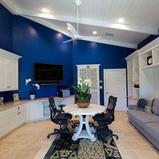 マイアミの中くらいのトロピカルスタイルのおしゃれな書斎 (青い壁、トラバーチンの床、造り付け机、ベージュの床) の写真