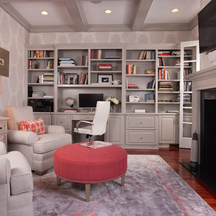 Inspiration for a mid-sized traditional home office in Atlanta with medium hardwood floors, a two-sided fireplace, a built-in desk, a library and multi-coloured walls.