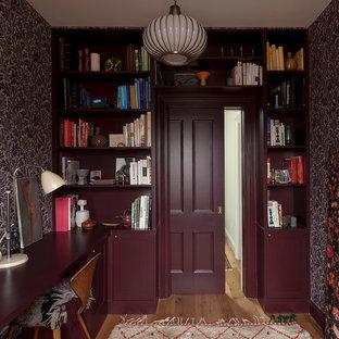 Inredning av ett klassiskt arbetsrum, med lila väggar, mellanmörkt trägolv, ett inbyggt skrivbord och ett bibliotek