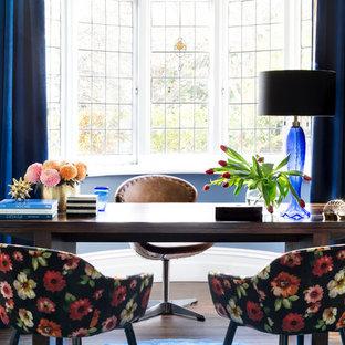 Cette photo montre un bureau chic de taille moyenne avec un mur bleu, un sol en bois foncé, un bureau indépendant et un sol marron.
