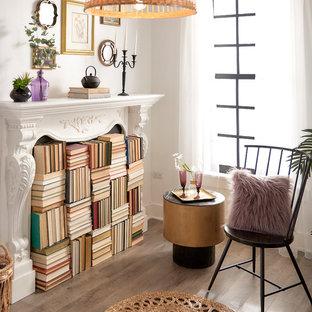Ispirazione per un piccolo studio eclettico con libreria, pareti bianche, parquet chiaro, camino classico, cornice del camino in intonaco e pavimento marrone