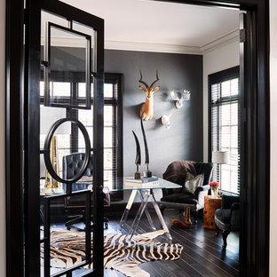 Inspiration för klassiska hemmabibliotek, med svarta väggar, mörkt trägolv, ett fristående skrivbord och svart golv