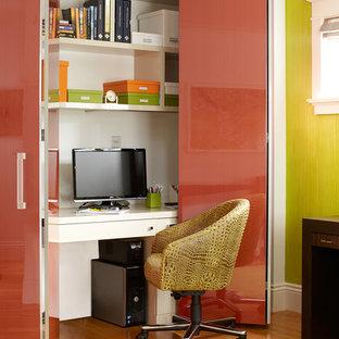Immagine di un piccolo studio minimal con pareti verdi, pavimento in legno massello medio e scrivania incassata