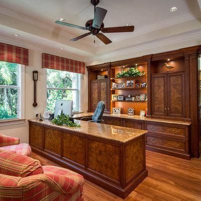 Elegant built-in desk medium tone wood floor study room photo in Miami with beige walls