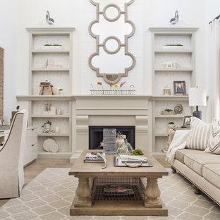 Foto de despacho campestre con paredes blancas, suelo de madera clara, chimenea de doble cara y escritorio independiente