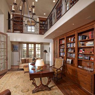 Großes Mediterranes Lesezimmer ohne Kamin mit weißer Wandfarbe, dunklem Holzboden, freistehendem Schreibtisch und braunem Boden in Houston