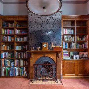 メルボルンの中くらいのトラディショナルスタイルのおしゃれな書斎 (グレーの壁、カーペット敷き、標準型暖炉、木材の暖炉まわり、自立型机、オレンジの床) の写真