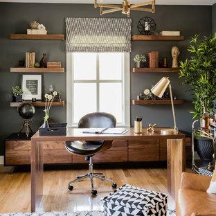 Modernes Arbeitszimmer mit Arbeitsplatz, grauer Wandfarbe, braunem Holzboden, freistehendem Schreibtisch und braunem Boden in Boston