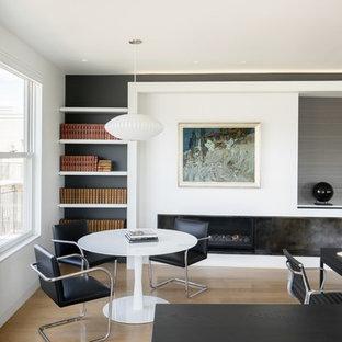 Modelo de despacho moderno, de tamaño medio, con paredes blancas, suelo de madera clara, chimenea lineal, marco de chimenea de yeso, escritorio empotrado y suelo beige