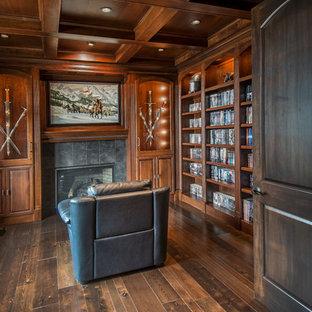 Foto på ett amerikanskt arbetsrum, med mörkt trägolv, en standard öppen spis och en spiselkrans i trä