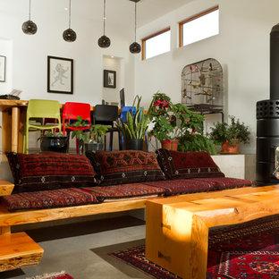 カルガリーの中サイズのコンテンポラリースタイルのおしゃれなホームオフィス・仕事部屋 (コンクリートの床、ライブラリー、白い壁、薪ストーブ、金属の暖炉まわり、自立型机、ベージュの床) の写真
