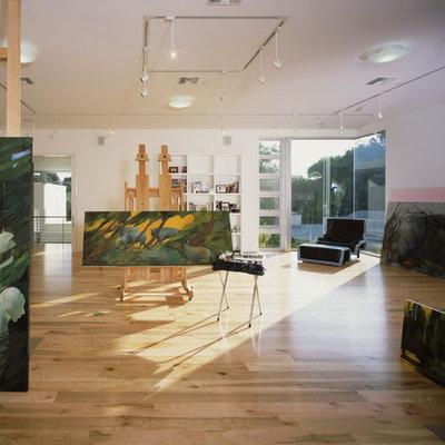 Example of a minimalist medium tone wood floor and beige floor home studio design in Los Angeles with white walls