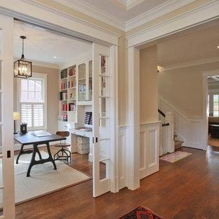 Inredning av ett klassiskt arbetsrum, med beige väggar, mellanmörkt trägolv och ett fristående skrivbord