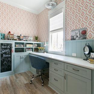 Inspiration för ett maritimt hemmabibliotek, med orange väggar, mellanmörkt trägolv, ett inbyggt skrivbord och brunt golv