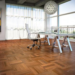 На фото: рабочее место среднего размера в современном стиле с белыми стенами, паркетным полом среднего тона, отдельно стоящим рабочим столом и оранжевым полом без камина с