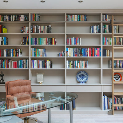 Home office library - large transitional freestanding desk light wood floor and gray floor home office library idea in Essex with beige walls
