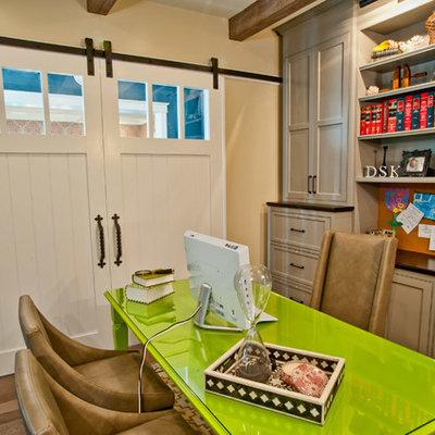 Elegant freestanding desk dark wood floor home office photo in Los Angeles with beige walls