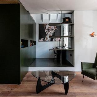 Design ideas for a small contemporary study in London with white walls, a built-in desk and black floors.