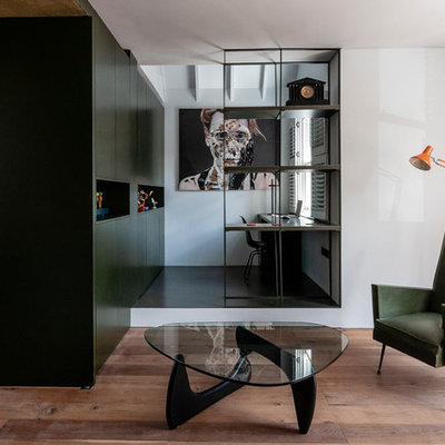 Inspiration for a small contemporary built-in desk black floor study room remodel in London with white walls