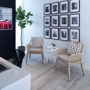 Cette image montre un petit bureau nordique de type studio avec un mur blanc, un sol en bois clair, un bureau indépendant et un sol beige.
