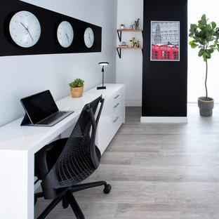 Пример оригинального дизайна: маленькая домашняя мастерская в скандинавском стиле с отдельно стоящим рабочим столом, серыми стенами и полом из винила без камина