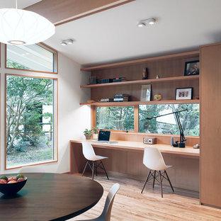 Modelo de despacho vintage, pequeño, sin chimenea, con paredes blancas, suelo de madera clara y escritorio empotrado