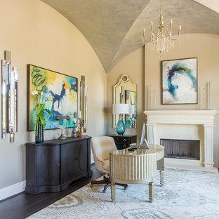 ヒューストンの広い地中海スタイルのおしゃれな書斎 (ベージュの壁、濃色無垢フローリング、標準型暖炉、自立型机、漆喰の暖炉まわり) の写真
