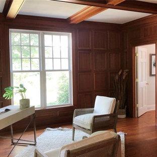 Klassisk inredning av ett mellanstort hemmabibliotek, med mellanmörkt trägolv, en standard öppen spis, en spiselkrans i sten och ett fristående skrivbord