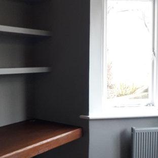 Idee per un ufficio contemporaneo di medie dimensioni con pareti blu, pavimento in legno verniciato, camino classico, cornice del camino piastrellata, scrivania incassata e pavimento marrone