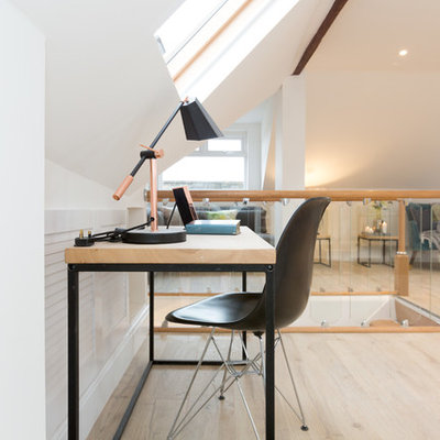 Example of a trendy freestanding desk light wood floor and beige floor home office design in London with white walls