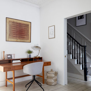 This is an example of a large midcentury study in London with white walls, painted wood flooring, a wood burning stove, a freestanding desk and beige floors.