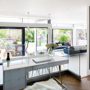 This is an example of a contemporary home office and library in London with white walls.