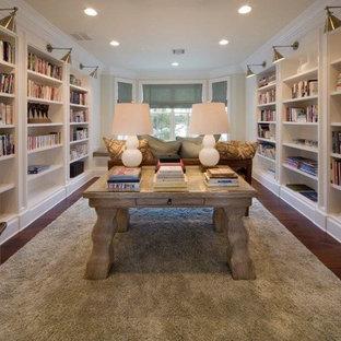 Bild på ett mycket stort vintage arbetsrum, med ett bibliotek, beige väggar, mörkt trägolv, ett fristående skrivbord och brunt golv