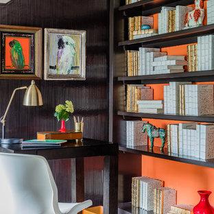 Modelo de despacho clásico renovado con parades naranjas, suelo de madera en tonos medios, escritorio independiente y suelo marrón