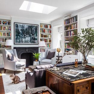ニューヨークの中くらいのトランジショナルスタイルのおしゃれなホームオフィス・書斎 (ライブラリー、標準型暖炉、石材の暖炉まわり、自立型机、茶色い床、白い壁、濃色無垢フローリング) の写真