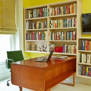Immagine di uno studio chic con pareti gialle, pavimento in legno verniciato e scrivania autoportante