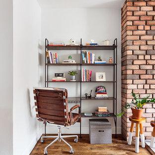 Esempio di un piccolo ufficio minimalista con pareti bianche, pavimento in legno massello medio, camino classico, cornice del camino in mattoni e scrivania autoportante