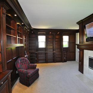 Ejemplo de despacho clásico, grande, con paredes azules, moqueta, chimeneas suspendidas, marco de chimenea de baldosas y/o azulejos y escritorio empotrado