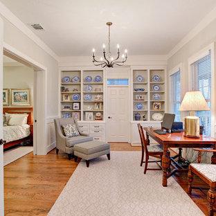 Study room - transitional freestanding desk medium tone wood floor and brown floor study room idea in Houston with gray walls