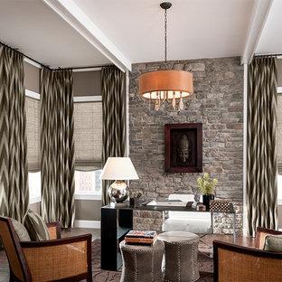 Mittelgroßes Asiatisches Arbeitszimmer mit Arbeitsplatz, grauer Wandfarbe, dunklem Holzboden, Kamin, Kaminumrandung aus Stein und freistehendem Schreibtisch in Cleveland