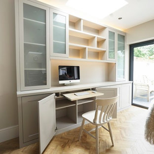 This is an example of a small contemporary study in Buckinghamshire with beige walls, light hardwood flooring, a built-in desk and beige floors.