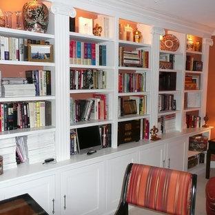 На фото: домашняя библиотека среднего размера в классическом стиле с оранжевыми стенами, ковровым покрытием, отдельно стоящим рабочим столом и бежевым полом без камина с