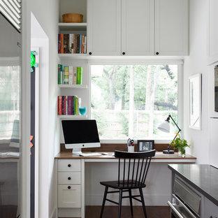 Klassisches Arbeitszimmer mit braunem Holzboden, weißer Wandfarbe, Einbau-Schreibtisch und braunem Boden in Austin