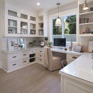 Klassisches Arbeitszimmer mit weißer Wandfarbe, braunem Holzboden, Einbau-Schreibtisch und braunem Boden in Orange County