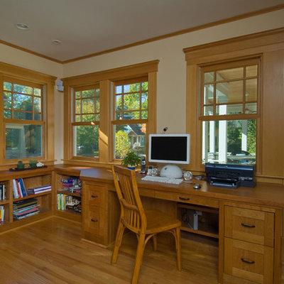 Mid-sized elegant built-in desk medium tone wood floor study room photo in Detroit with beige walls